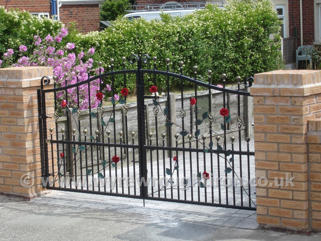 Double arch wrought iron gates with ball railheads, cage twists and hand finished roses, vines and leaf detail. Galvanised and powder coated in black for Fleetwood customer.