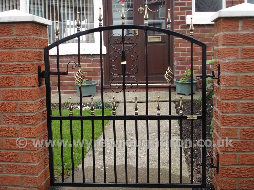 Single arch topped garden gate with railheads, cage twist and scrollwork. Galvanised and powder coated black for Blackpool household.