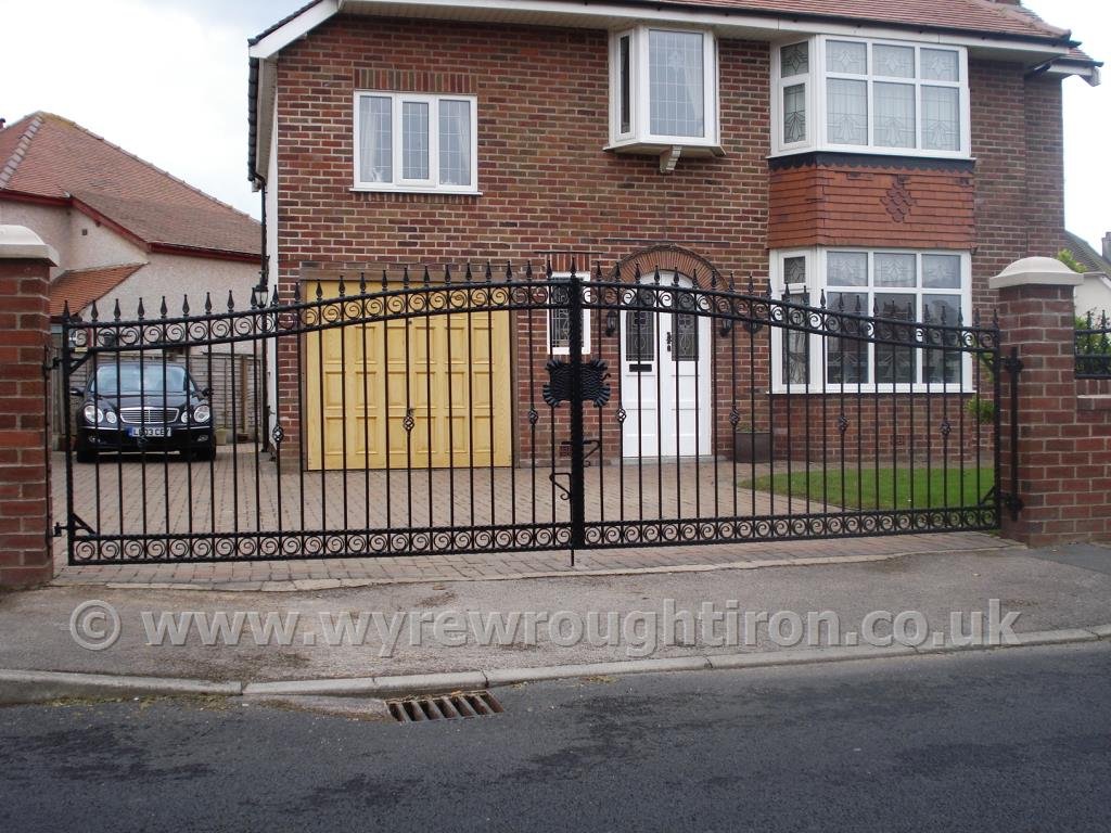 Wide span double arch driveway gates with railheads and scrolled tail circles, installed to a house in Cleveleys. Galvanised and powder coated in black
